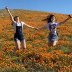 Two women jumping in poppy field